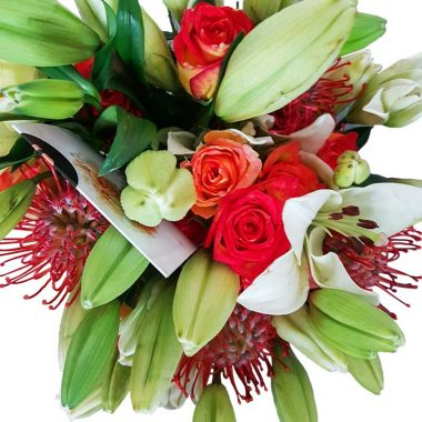 Colorful mic of reds orange and whites, roses lilies and pin cushions